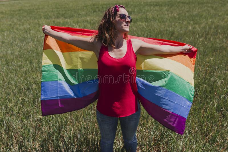 Woman holding the Gay Rainbow Flag on a green meadow outdoors. Happiness, freedom and love concept for same sex couples. LIfestyle. Outdoors royalty free stock photos