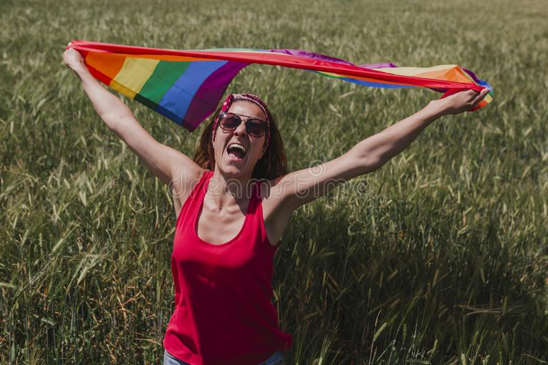 Woman holding the Gay Rainbow Flag on a green meadow outdoors. Happiness, freedom and love concept for same sex couples. LIfestyle. Outdoors stock photos