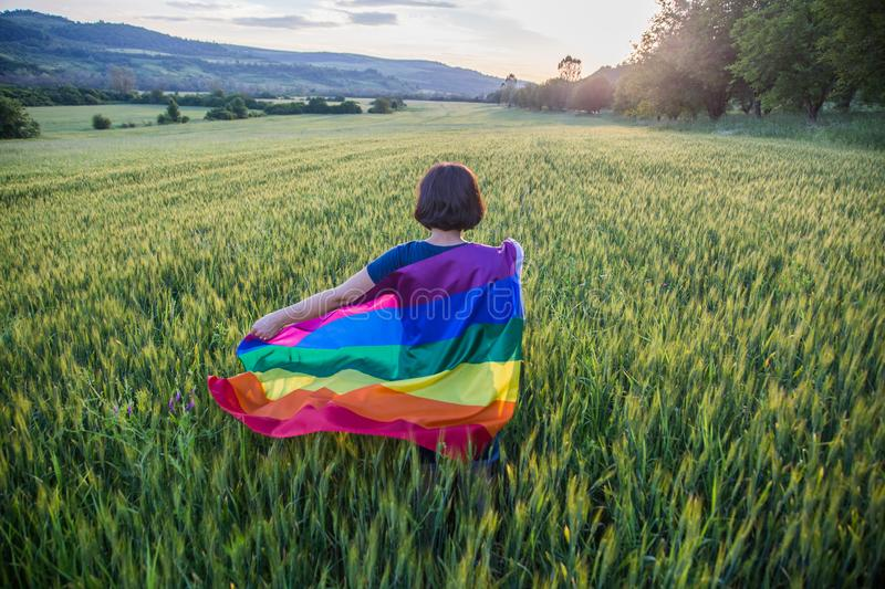 Woman holding the Gay Rainbow Flag on a green meadow outdoors. Happiness, freedom and love concept for same sex couples royalty free stock photo
