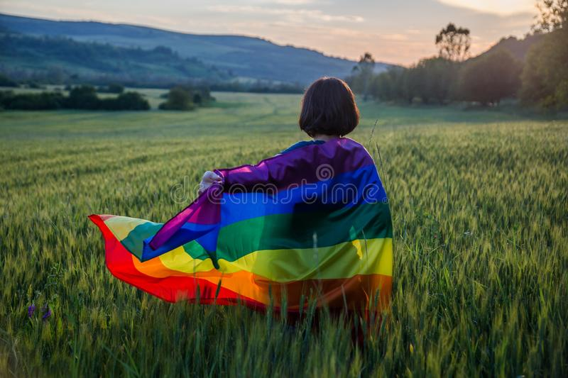 Woman holding the Gay Rainbow Flag on a green meadow outdoors. Happiness, freedom and love concept for same sex couples. Woman holding the Gay Rainbow Flag on a stock images