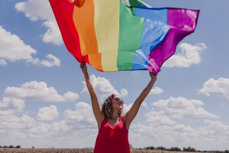 Woman holding the Gay Rainbow Flag over blue and cloudy sky outdoors. Happiness, freedom and love concept for same sex couples. LIfestyle outdoors stock images