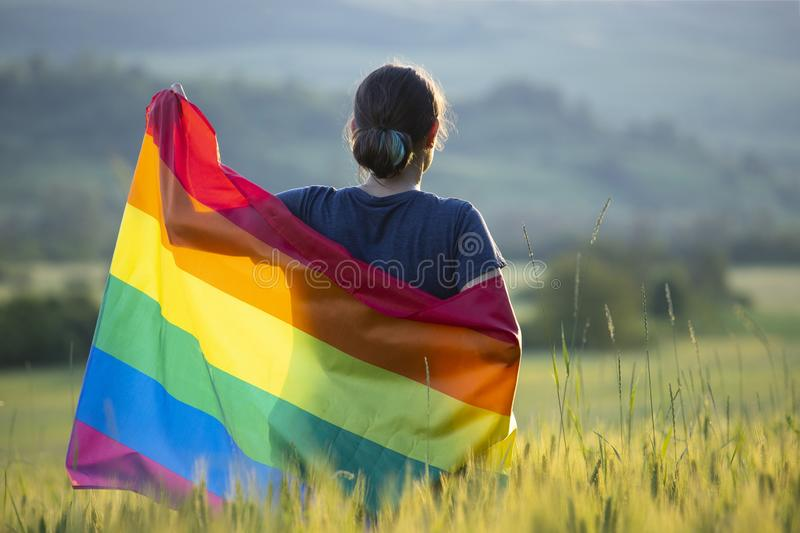 Young woman with LGBT flag. Woman holding a Gay Rainbow Flag over blue summer sky. Bisexual,gay, lesbian, transsexual symbol. Happiness, freedom and love concept stock image