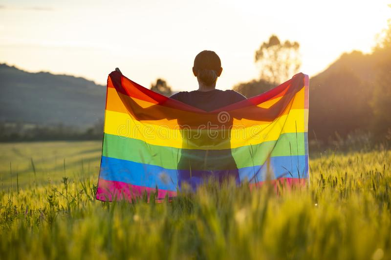 Young woman with LGBT flag. Woman holding a Gay Rainbow Flag over blue summer sky. Bisexual,gay, lesbian, transsexual symbol. Happiness, freedom and love concept stock photography