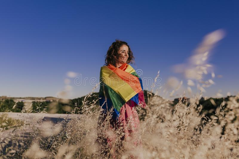 Woman holding the Gay Rainbow Flag at sunset. Happiness, freedom and love concept for same sex couples. LIfestyle outdoors stock photos