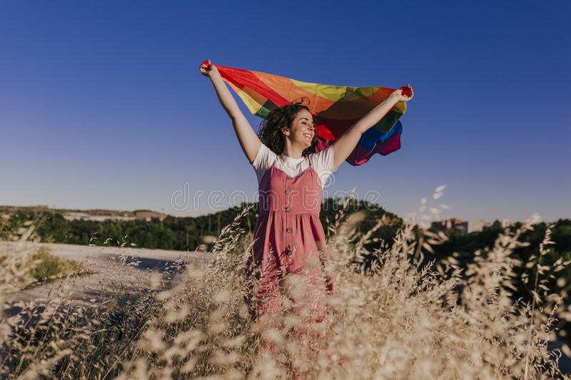 Woman holding the Gay Rainbow Flag at sunset. Happiness, freedom and love concept for same sex couples. LIfestyle outdoors royalty free stock photos