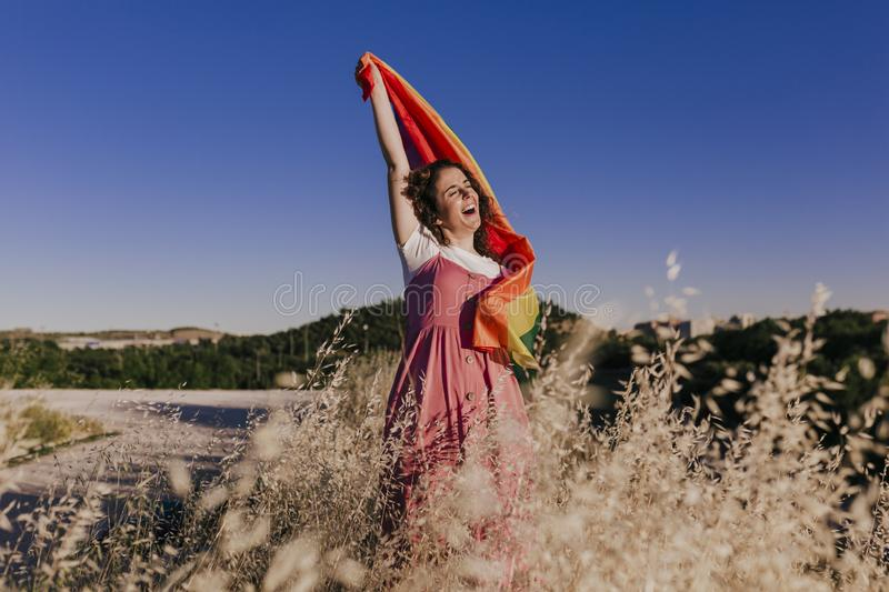 Woman holding the Gay Rainbow Flag at sunset. Happiness, freedom and love concept for same sex couples. LIfestyle outdoors royalty free stock image