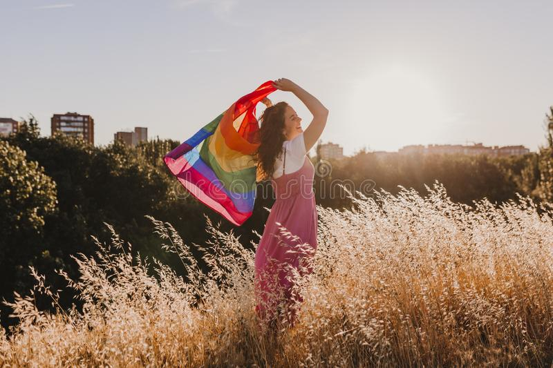 Woman holding the Gay Rainbow Flag at sunset. Happiness, freedom and love concept for same sex couples. LIfestyle outdoors royalty free stock images