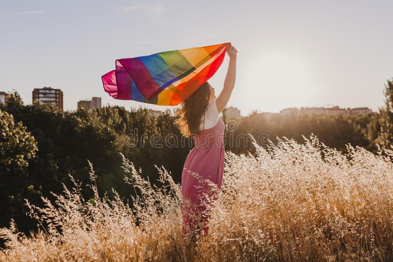 Woman holding the Gay Rainbow Flag at sunset. Happiness, freedom and love concept for same sex couples. LIfestyle outdoors royalty free stock photo