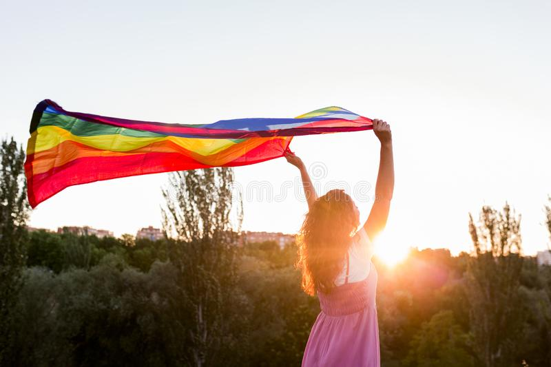Woman holding the Gay Rainbow Flag at sunset. Happiness, freedom and love concept for same sex couples. LIfestyle outdoors stock photography