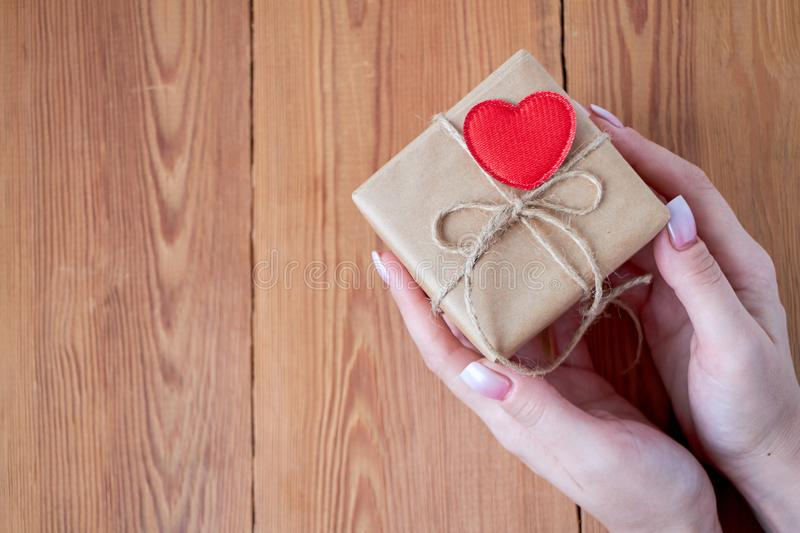 Woman holding a gift box in a gesture of giving. stock image