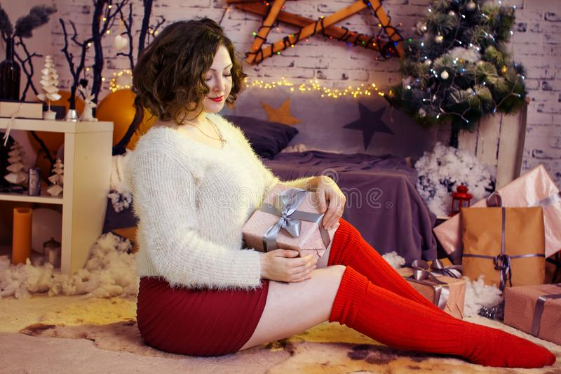 Happy woman with gift at Christmas tree royalty free stock image