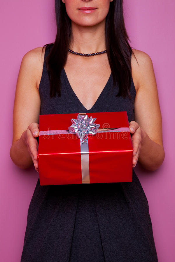 Woman Holding A Gift Wrapped In Red Paper Stock Image