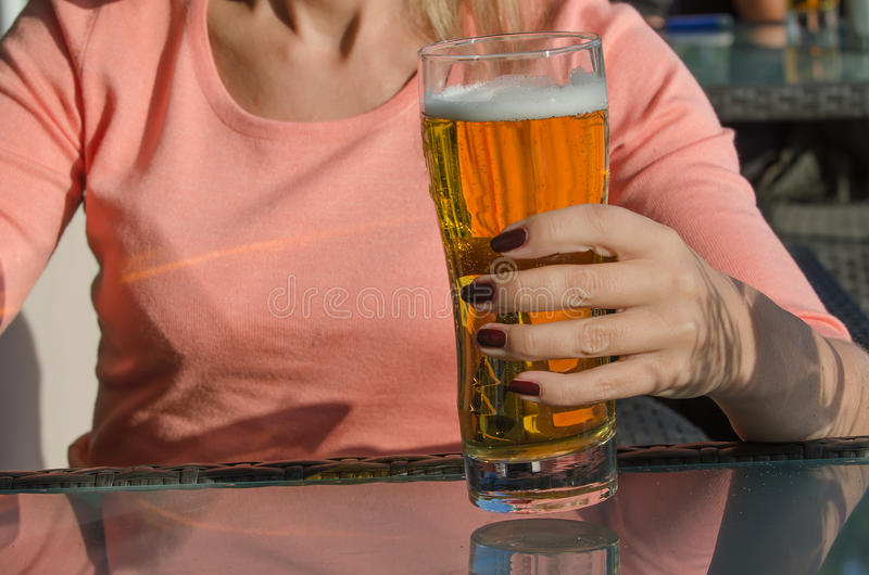 Woman holding a glass of beer. Hand of woman holding a glass of beer stock image