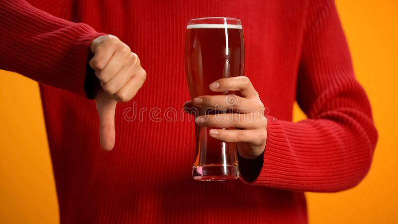 Woman holding glass of beer showing thumbs down, drunk driving danger, alcohol. Stock photo royalty free stock images