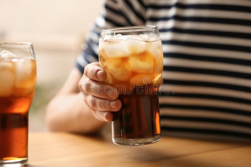 Woman holding glass of cola with ice at table. Closeup royalty free stock images