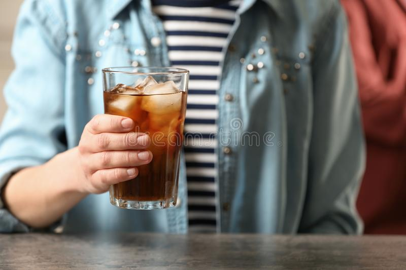 Woman holding glass of cola with ice at table. Closeup stock image