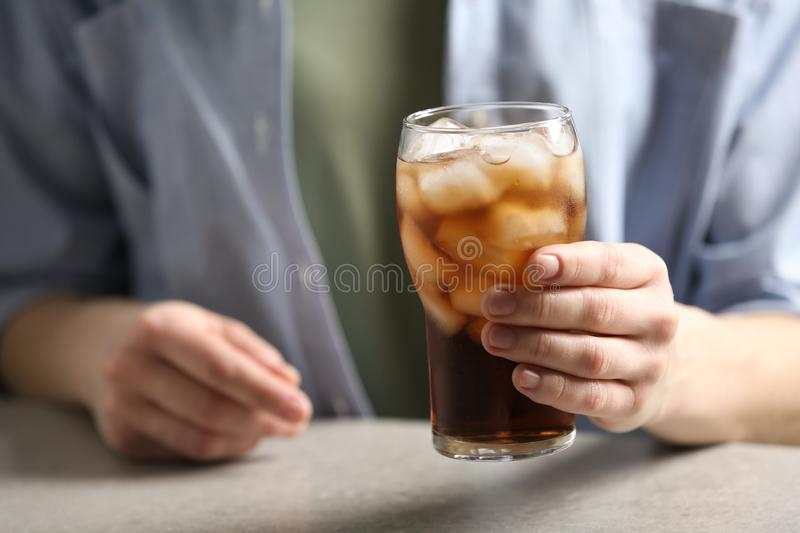 Woman holding glass of cola with ice at table. Closeup stock photography