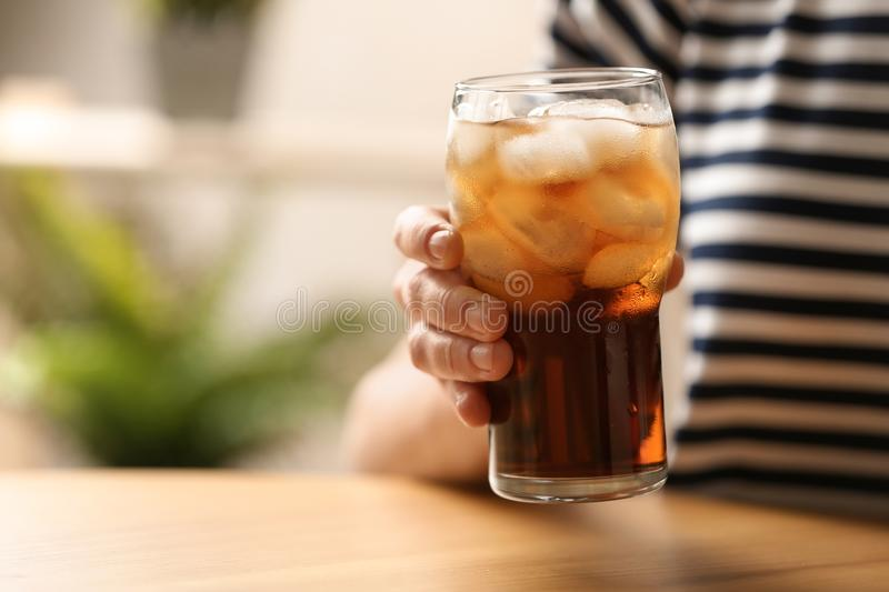 Woman holding glass of cola with ice at table. Closeup. Space for text royalty free stock image