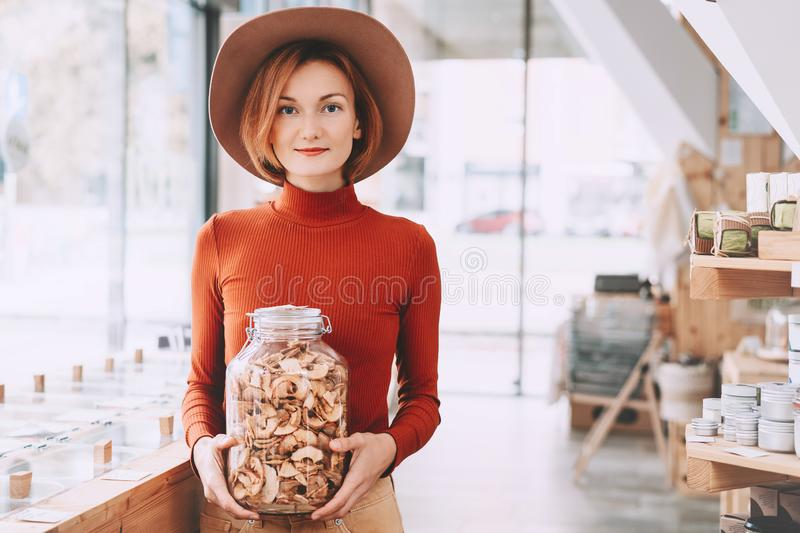 Woman holding glass jar with groceries in zero waste shop royalty free stock image