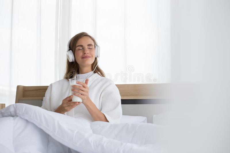 Woman holding glass of milk and listening relax song at music application in the morning on the bed stock photo
