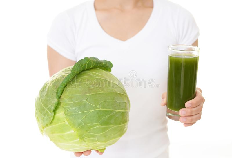 A glass of vegetable juice. Woman holding a glass of vegetable juice royalty free stock photo