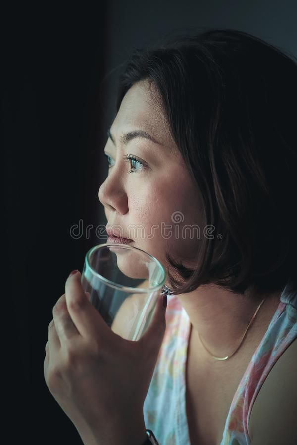 The woman is holding a glass of water with water to drink after waking up in the morning stock image