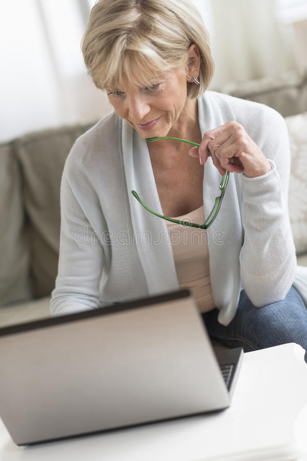 Free Woman Holding Glasses While Using Laptop Royalty Free Stock Photos - 46372578