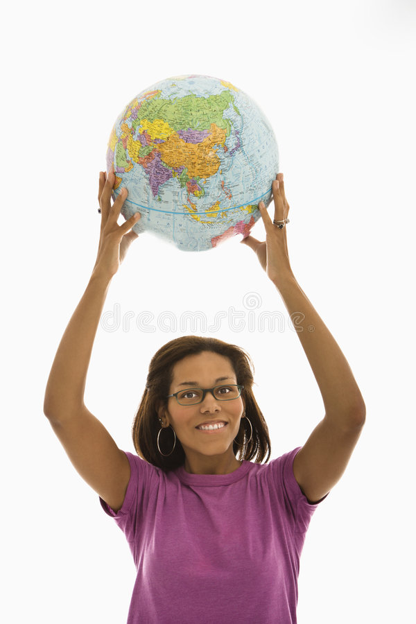 Woman holding globe. African American mid adult woman holding globe over head and smiling at viewer stock photography