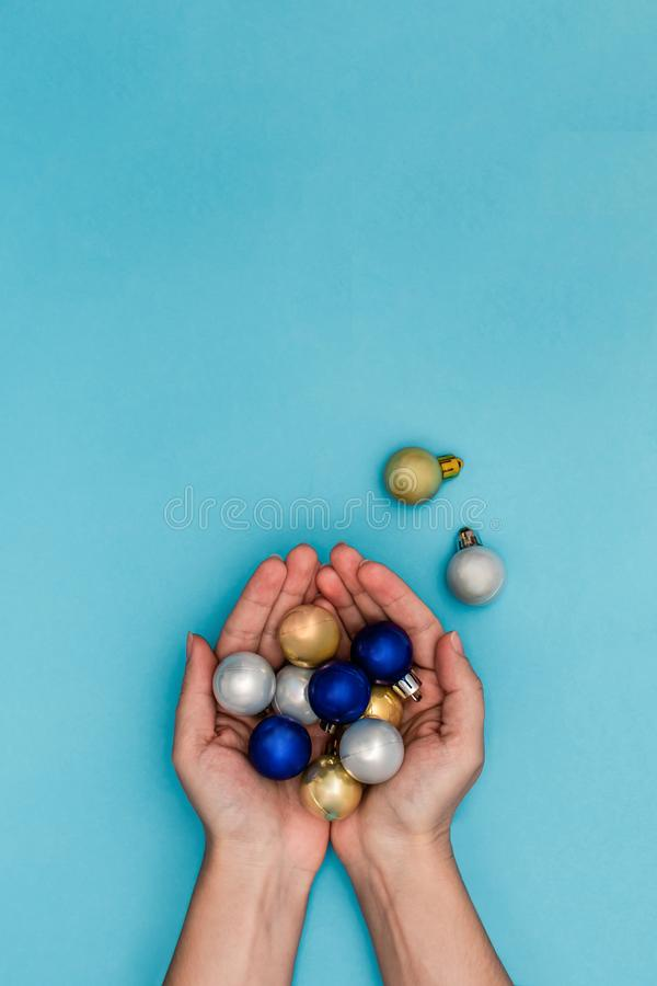 Woman holding a golden Christmas ball in a hands on the blue background stock image