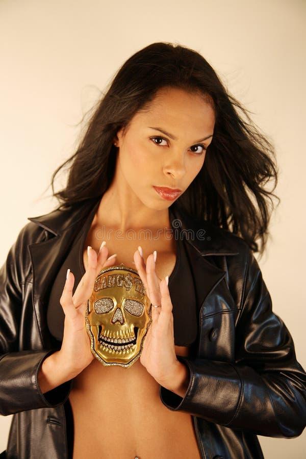 Woman holding golden skull medallion. Woman holding a golden skull medallion with both hands royalty free stock images