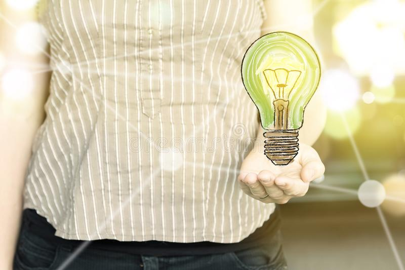 Woman holding a green light bulb with as `green thinking` concept on a sunny day.  stock images