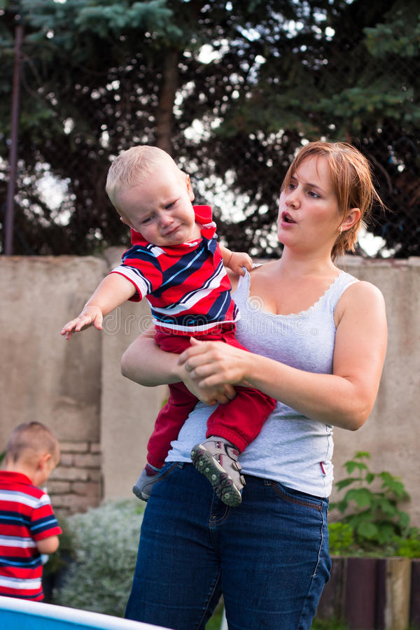 Woman holding grumpy crying toddler boy outdoors stock image
