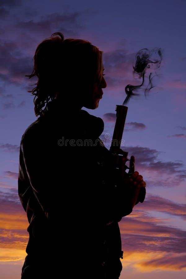 Woman holding a gun blowing silhouette profile. A silhouette of a woman blowing the smoke off her pistol royalty free stock photo