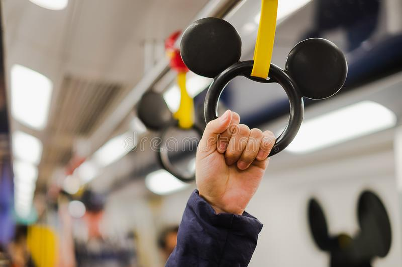 Woman holding hand grip in Disney Line MTR inside from Sunny bay to Hong Kong Disneyland resort, landmark for tourist attraction; stock photos