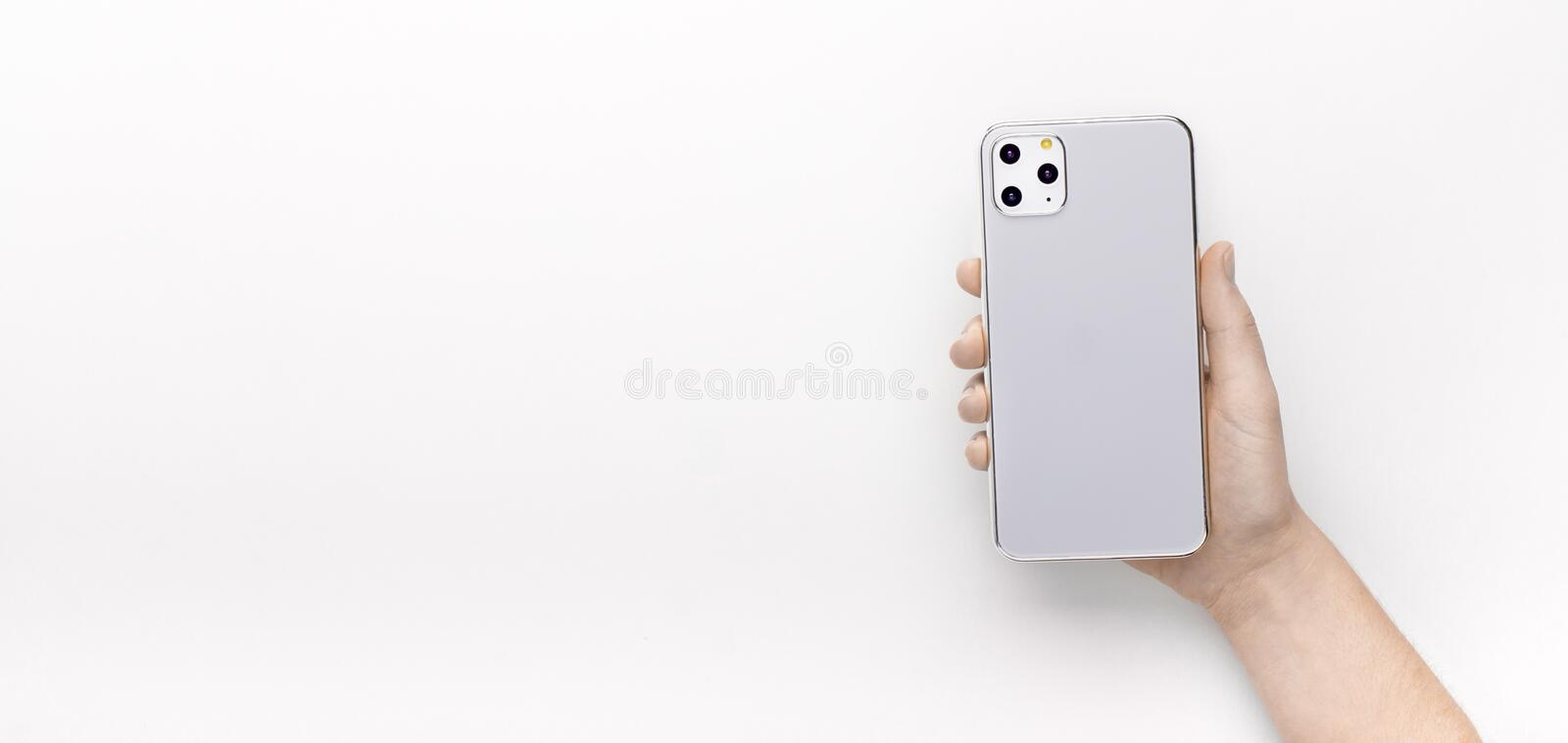 Woman holding in hand new 11 IPhone Pro with three cameras royalty free stock image