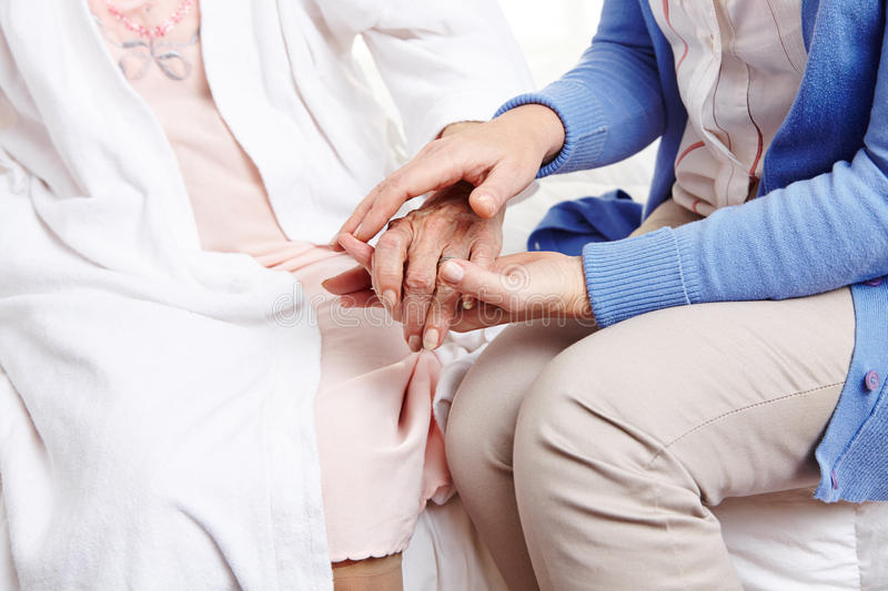 Woman holding hand of senior woman stock images