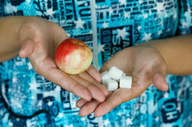 Woman holding in hands apple and sugar cubes. Female choose between fruit is healthy food and sweet is unhealthy junk foods royalty free stock photos