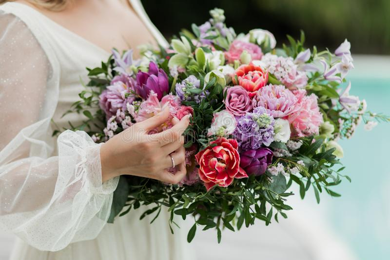 Woman holding big wedding bouquet close up. Red and pink tulips, roses, peony. Woman holding in hands big wedding bouquet close up. Red and pink tulips, roses stock photography