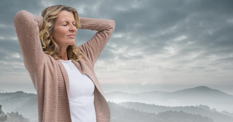 Woman holding hands on head practicing casual mindfulness in front of mountain landscape. Digital composite of Woman holding hands on head practicing casual stock photos