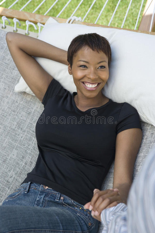 Woman Holding Hands Of Man On Hammock royalty free stock photography