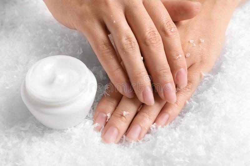 Woman holding hands near jar of cream on decorative snow. stock images