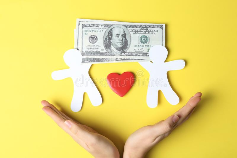 Woman holding hands near paper silhouettes of people, heart and money bills on color background, top view. stock image