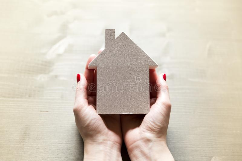 Woman holding in hands small white model house as a sign of protection, insurance and importance of own home royalty free stock photos