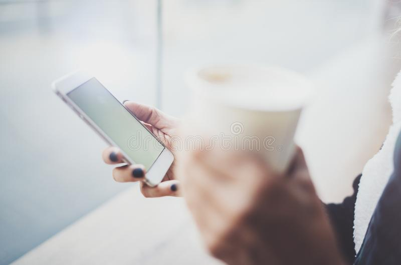 Woman holding hands smartphone and texting message.Female hands using mobile phone.Closeup on blurred background.Flares. Bokeh effects. Mock-up royalty free stock photos