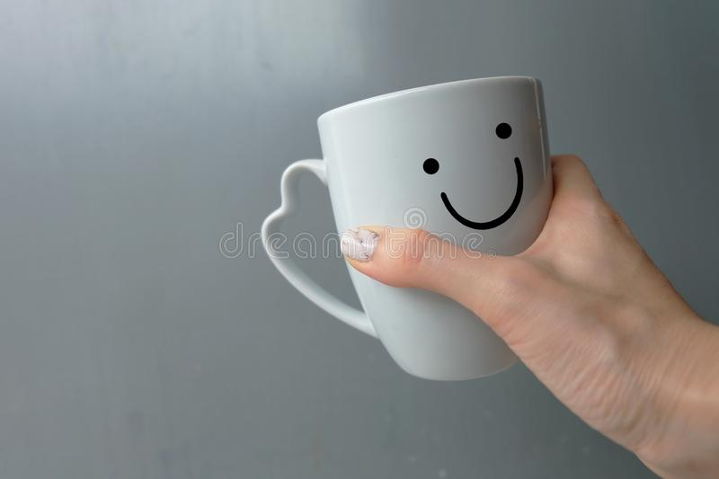 Woman Holding Happy Smile White Cup of Coffee. Close Up Granite Gray Nail Polish on the Background royalty free stock image