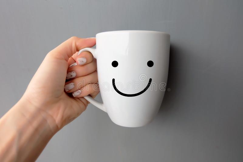 Woman Holding Happy Smile White Cup of Coffee. Close Up Granite Gray Nail Polish on the Background stock images