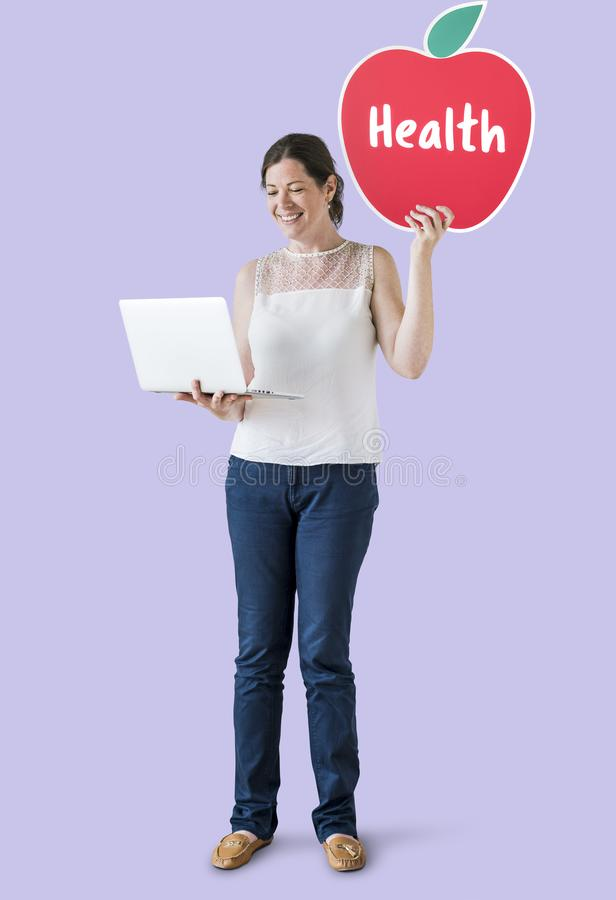 Woman holding a health icon and using a laptop stock photography