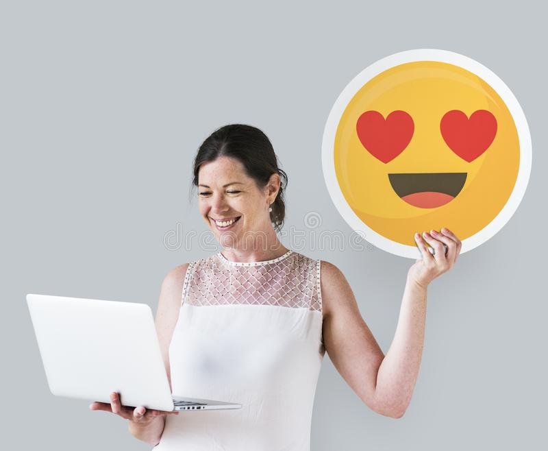 Woman holding a heart eyes emoticon and a laptop stock photos