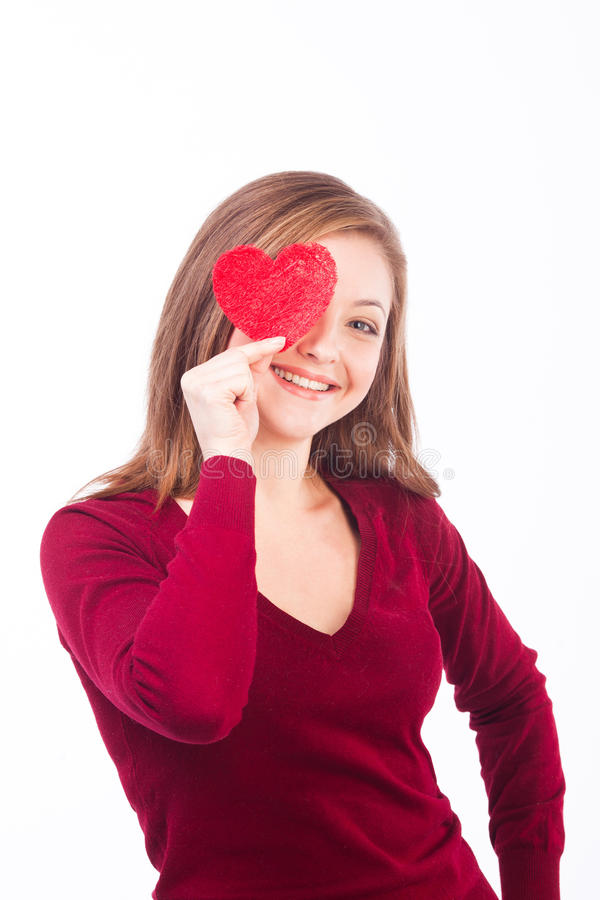 Woman holding heart shape to her face. Studio whot of young caucasian smiling woman isolated on white background holding heart shape to her face royalty free stock photography