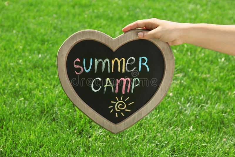 Woman holding heart shaped blackboard with text SUMMER CAMP and drawing royalty free stock image
